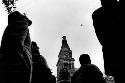 A noon-time crowd watches Tino Wallenda, of the famous Flying Wallenda family, perform his high wire act to a famous tower in downtown Denver, Co., on May 23, 1987.