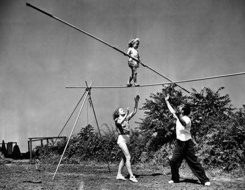 Carla Wallenda carries on as the fourth generation of the famous Wallenda family of circus aerialists on July 4, 1941. Using a 20-foot pole to balance herself, Carla walks sure-footed along a pipe 10 feet off the ground. Her mother Helen and father Karl are below.