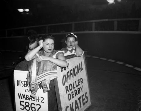 Chicago Westerners Roller Derby skaters Ann Pernice, 19, and Eleanor Weber, 24, watch from the penalty box at the Coliseum at a Roller Derby in 1950. During the month of November, two teams of ten men and women each, skated against each other, sometimes traveling at speeds up to 30 miles an hour.