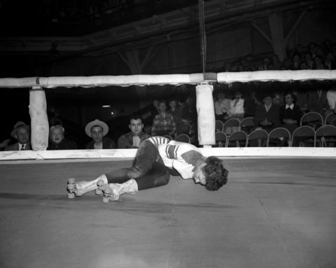 """Virginia Rushing, 22, from Oklahoma City, doubles over in pain after receiving a belt in the midsection during a roller derby at the Coliseum in 1951. The Tribune reported Rushing as saying, """"This is a really terrific profession."""" Rushing, who grew bored with office work, continued saying, """"I love it. It's the most exciting thing a girl can do."""" By 1951, Rushing had already suffered a broken pelvis and ankle."""