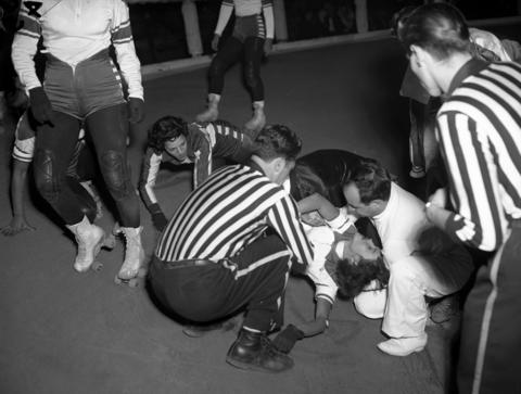 A referee and a doctor aid Betty Boyd, 23, of the Jersey Jolters, who was knocked out in a fall during a roller derby at the Coliseum in 1951. At the time, Boyd had a daughter named Donna Jo, 2, who would travel with her to matches. Boyd is originally from Chattanooga, Tenn.