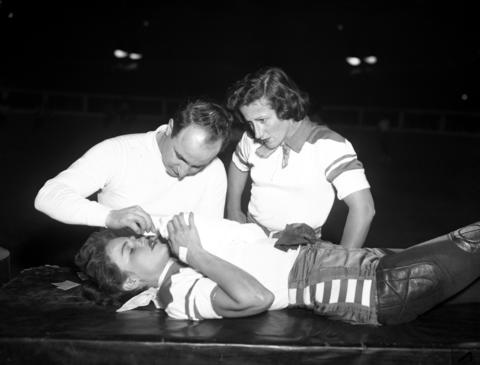 Betty Boyd of the Jersey team is treated by Dr. James Alvian as her teammate and captain Annis Jansen watches at a roller derby at the Coliseum on Feb. 15, 1951.