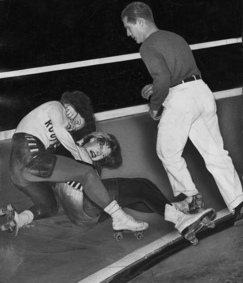 """A referee goes in to break up a skirmish during a Coliseum match in 1941 between Virginia Balzer, left, of the Chicago team, and Virginia Ogden, of the California team. According to the Tribune, """"the referee revealed the loss of some hair and a few loose teeth."""""""