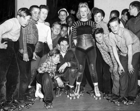 """Over 1,000 newspaper carriers for The Herald-American were treated to a free night of roller derby at the Michigan Avenue Armory, located at Michigan Ave. and 16th St., in April 1943. Some of them gathered around Chicago roller derby star Dorothy """"Johnnie the blonde bombshell"""" Kobusch. Kobusch was born in the Edgewater neighborhood of Chicago."""