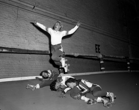 """Marjorie Clare """"Toughie"""" Brasuhn (she went by the first name of Midge) flies over Betty Clements, Mary Lou Palermo and Harriette Topel at a roller derby at the Coliseum in Nov. 1953. Brasuhn was the sport's most recognized celebrity, known to fans as Toughie, and played for teams in New York and New Jersey during the 1940s and 50s."""