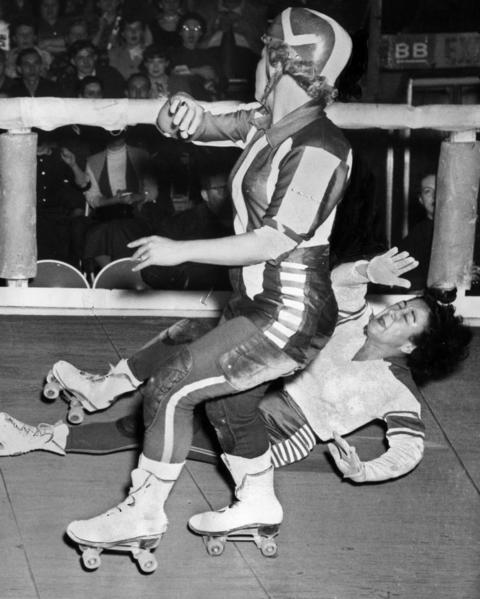 """Mary Youpelle of the Chicago Westerners hits the floor after being blocked by Midge """"Toughie"""" Brasuhn of the Brooklyn Red Devils in a roller derby at the Coliseum on Oct. 29, 1952."""