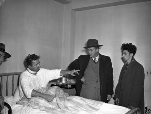 """An injured Nick Kuesis points to his brother's killer and the man who shot him in the neck, James Morelli, 20, right, circa December 1947. """"That's the dirty bastard that killed my brother,"""" said Kuesis. At left is Detective Emil Smicklas, and second from right is Detective Charles Malek."""