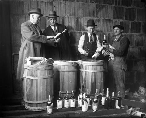 From left, Capt. A.C. Townsend, U.S. Marshal Palmer Anderson, Deputy U.S. Marshal A.J. Jostock and a laborer look over confiscated liquor at a federal warehouse, circa April 1925. The men were ordered to clear out the warehouse for seized liquor to make room for Army purposes.