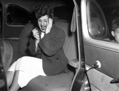 """Agnes Stathatos cries after identifying her brother George Stathatos' body. The victim was found in his car with two bullets in his head, his hands and feet tied together and his mouth taped shut in the 600 block of N. Troy Street on May 22, 1948. Stathatos, a former tavern owner and known gambler, had not worked for three years but, according to the Tribune, he """"always had money."""" It was suspected that Stathatos and several gang members specialized in robbing syndicate handbooks and were tortured and killed in retaliation."""