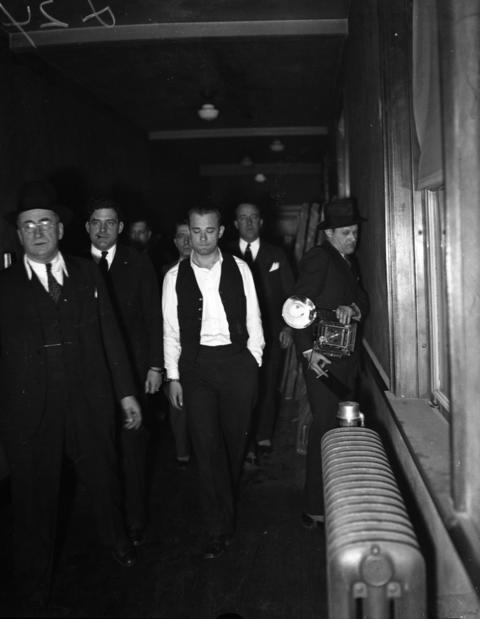 John Dillinger, center, is led through the Crown Point, Ind., court building on Jan. 31, 1934 to be viewed by witnesses from the First National Bank robbery that occurred on Jan. 15, 1934 in East Chicago, Ind. With Dillinger is Chief Deputy Sheriff Carroll Holly of Crown Point.