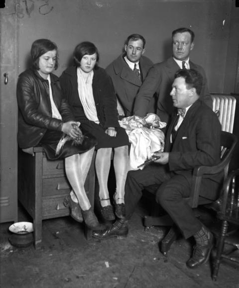 """Girl bandits Jean Buttick, 15, and Anna Varich, 16, were caught red-handed while looting the bungalow of Louis Oehler in the 6100 block of South California Avenue on March 20, 1927. The Tribune reported that when the police seized Varich in the kitchen, """"she spilled rings, bracelets, beaded bags, and what not from every part of her clothes. When they shook her she literally dripped booty."""" Police officers believe the two bandits had looted about a dozen other homes in the prior two weeks. With Buttick and Varich are Charles Goss, Bert Harlem and Sgt. William H. Doyle (seated)."""