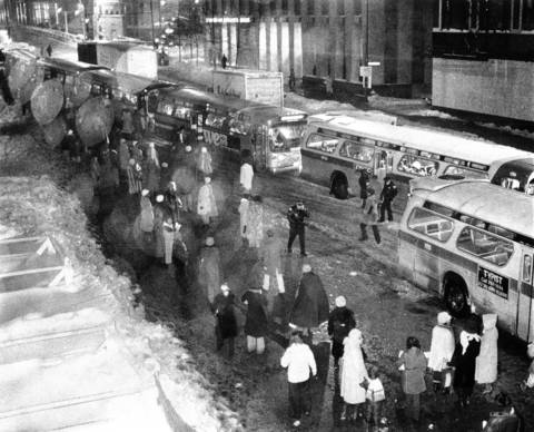 Standing in an icy drizzle, Chicagoans line up at State and Lake Streets on Jan. 19, 1979, to get aboard one of a caravan of CTA buses.