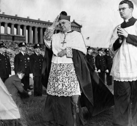 Archbishop Samuel Stritch, center, blesses the crowd as he walks in an ecclesiastical procession at Soldier Field in 1945.