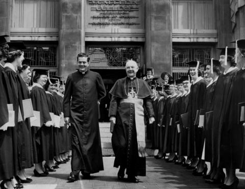 Cardinal Samuel Stritch, right, and the Rev. William P. Murphy of Mundelein College walk between lines of graduating seniors at the 20th annual commencement at the school June 5, 1951.