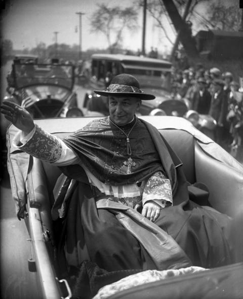 Cardinal George Mundelein raises his right hand to bestow his blessings upon the crowd May 11, 1924, during a parade in his honor after his return home from Rome after being appointed cardinal.