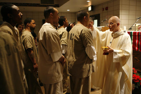 Cardinal Francis George gives Holy Communion to prisoners in the maximum security wing of Cook County Jail on Christmas Day 2006 in Chicago.
