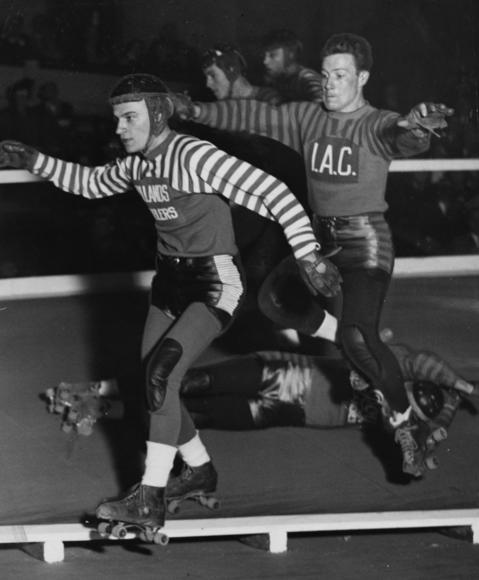 Though the women of roller derby were more popular with fans, men were very much a part of the sport. Here, Bill Bogash, left, and Bob Satterfield, step over a fallen skater during a Coliseum match in October 1940. Bogash was the leader of the Chicago team and Satterfield, a New Yorker, would go on to coach the Chicago roller derby team and marry one of its' players, Betty Boyd. Betty and Bob had a daughter, Donna, who traveled with the team.