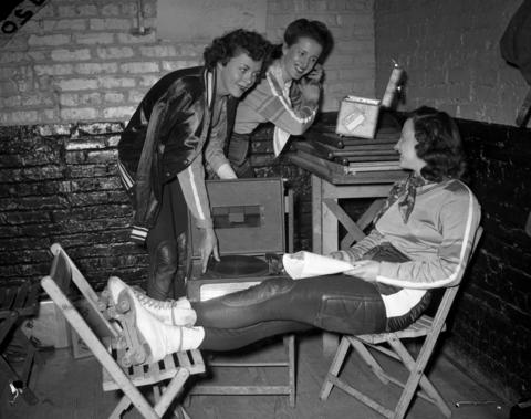 Monte Jean Payne, Chicago roller derby captain, Marilyn Bullock and Catherine Virva, of McKinley High School in Chicago, are in the dressing room during a roller derby at the Coliseum on April 1, 1949. Bullock had been skating with the derby for four years and lived in Hollywood, Ca., but was originally from Chicago and attended Stewart Elementary School.