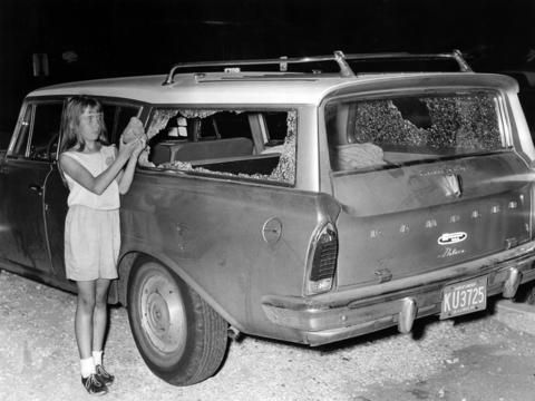 Sharon Fitzpatrick, 10, holds a rock as she stands beside her family's station wagon which was pelted by rocks during the rioting on Aug. 16, 1964, in Dixmoor, Ill. Fitzpatrick received a head laceration as the rocks smashed through the windows of the car as the family drove along 147th Street. She is standing outside the Ingalls Memorial Hospital in Harvey, Ill., where many of the injured were taken.