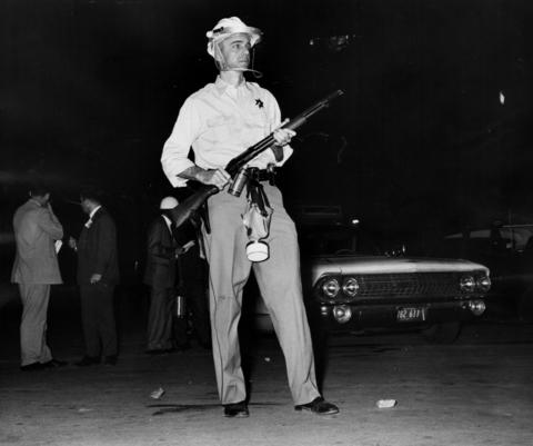 A police officer stands guard with riot gear during the second night of rioting in Dixmoor, Ill., on Aug. 17, 1964.