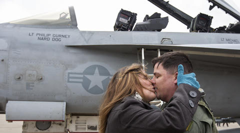 "Staff Photo Of The Week: Nov 8-Nov 14, 2014     Jodi Miller kisses her husband, Cmdr. Scott Miller, after he arrived with Strike Fighter Squadron VFA 213 ""Blacklions"" at Naval Air Station Oceana on Friday in Virginia Beach."