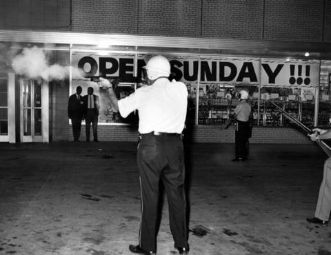 A policemen fires tear gas shells in an effort to disperse the throng of rioters in suburban Dixmoor, Ill., on Aug. 17, 1964. Rioting flared over the weekend near the Foremost Liquors store following an alleged theft attempt and scuffle between the owner of the store and a suspect. An attempt was made the prior night to burn the store after authorities had ordered it closed to prevent further demonstrations, but the arson effort failed.