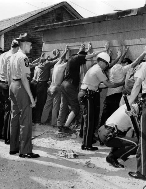 State and County police arrest nine men and one 14 year-old boy at the rear of Foremost Liquors store at 2240 W. 147th Street in Dixmoor, Ill., on Aug. 19, 1964. The men were accused of stealing whiskey from Foremost Liquors as the store was trying to remove its inventory due to the rioting. Three cases of whiskey were found in the field behind the store, along with a homemade bomb that had been left there on Monday.