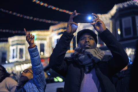 Onlookers take photos after the ceremonial lighting of the 34th Street Christmas lights Saturday night in Hampden.