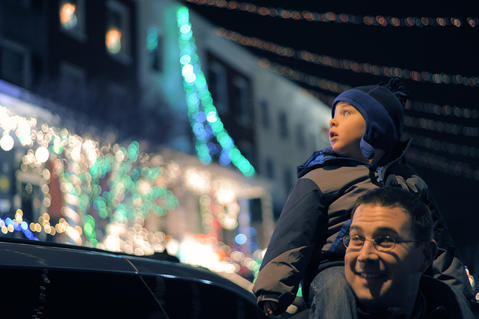 Travis Pendergast of Timonium looks back as his son Will Pendergast, 2, looks at animated displays during the annual 34th Street Christmas lighting ceremony Saturday.