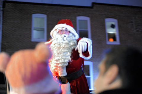 Santa Claus waves to a young admirer as he passes through the crowd during the annual 34th Street Christmas lighting ceremony Saturday.