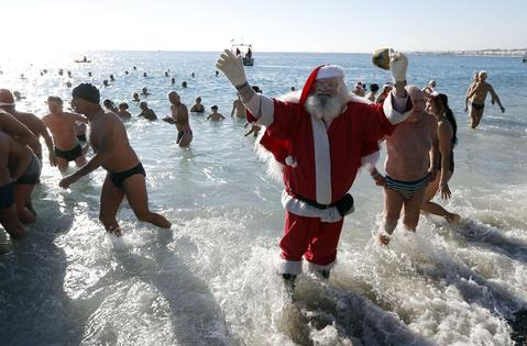 A man dressed as Santa Claus waves on December 15, 2013 on the beach in Nice as part of a traditional christmas winter sea swimming event.