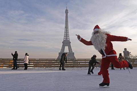 A man dressed as Santa Claus skates on an ice rink across from the Eiffel Tower as part of the Christmas holiday season preparations, in Paris December 12, 2013.