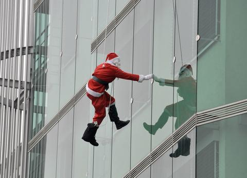 A member of the special police force dressed in a Santa suit, descends from the roof of a paediatric clinic in Ljubljana, as part of a Christmas performance for patients of the clinic, December 18, 2013.