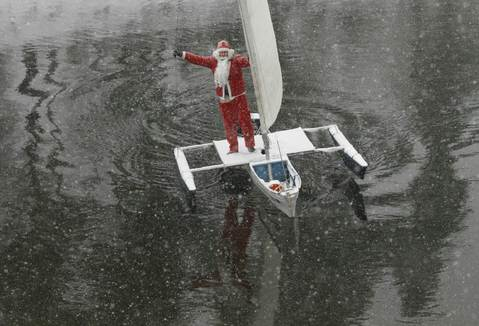 "A member of the ""Skipper"" yacht club dressed as Santa Claus, sails his trimaran to mark the ending of the sailboat season during heavy snowfall at an air temperature of above minus 8 degrees Celsius (17.6 Fahrenheit) on the Yenisei River, outside Russia's Siberian city of Krasnoyarsk, December 18, 2013."