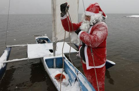 "A member of the ""Skipper"" yacht club dressed as Santa Claus, takes off rigging from his trimaran after sailing to mark the ending of the sailboat season during heavy snowfall at an air temperature of above minus 8 degrees Celsius (17.6 Fahrenheit) on the Yenisei River, outside Russia's Siberian city of Krasnoyarsk, December 18, 2013."