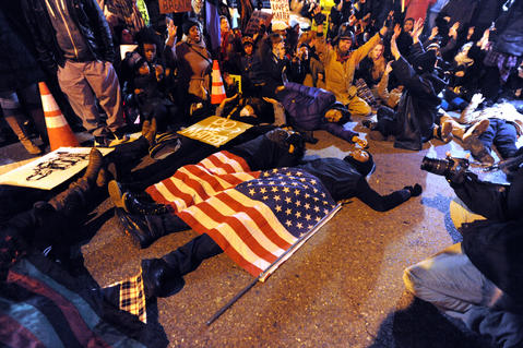 Demonstrators stage a die-in in attempt to disrupt the holiday lighting of the Washington Monument in Baltimore. Groups around the country are protesting a New York grand jury's decision not to indict officer Daniel Pantaleo in the Eric Garner case.