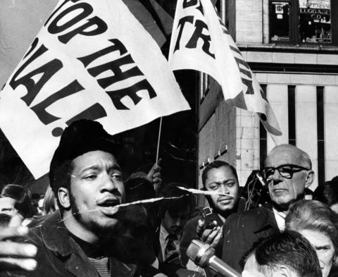 Fred Hampton, left, the head of the Illinois Black Panthers, and Dr. Benjamin Spock, right, rally with others against the trial of eight people accused of conspiracy to start a riot at the Democratic National Convention. The rally was held outside the Federal Building on Oct. 29, 1969. Editors note: There is damage to this historic print.