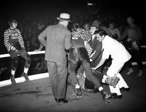 Louis Stasiuk, of the New York roller derby team, and Paul Gorski of the Chicago roller derby team, tangle and spill, then start to fight with Chicagoan Johnny Rosasco joining the fight during the sixth annual roller derby that opened at the Coliseum on Oct. 22, 1940. According to the Tribune, roller derby made its world debut in Chicago in 1934.
