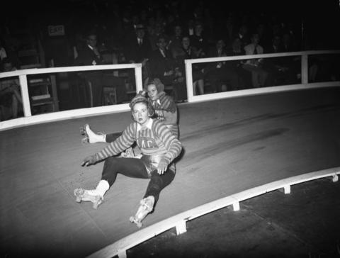 Ronnie Powell, front, and Jeanne Goette, rear, both of the New York team, take a seat during the sixth annual roller derby at the Coliseum on Oct. 22, 1940.