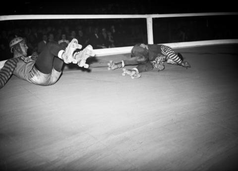 Louis Stasiuk, of the New York roller derby team, and Paul Gorski of the Chicago roller derby team, tangle and spill, during the sixth annual roller derby that opened at the Coliseum on Oct. 22, 1940.