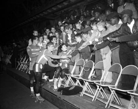 Chicago American news carriers wave their tickets to get autographed from Fred Noa, from left, Bert Wall, Dolores Doss and Bobbie Mateer, all of the Chicago Westerners roller derby team, on April 28, 1955, at the Coliseum.