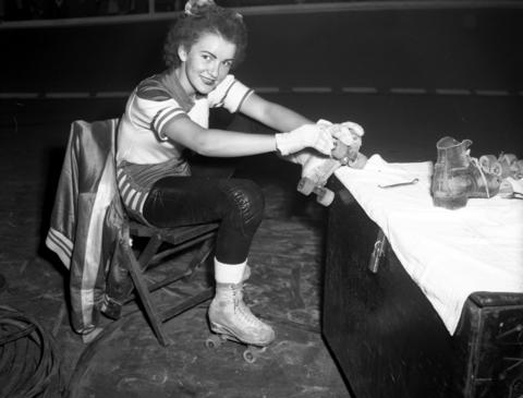 Mary Gray, 22, a member of the Chicago Westerners roller derby team, repairs her skates between periods at a roller derby at the Coliseum in 1950.