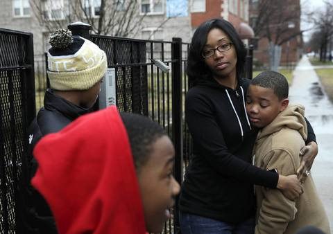 Hadiya Pendleton's 10-year-old brother, Nathaniel Pendleton, Jr., (right) is comforted by his aunt Kimiko Pettis outside Pendleton's South Side home.