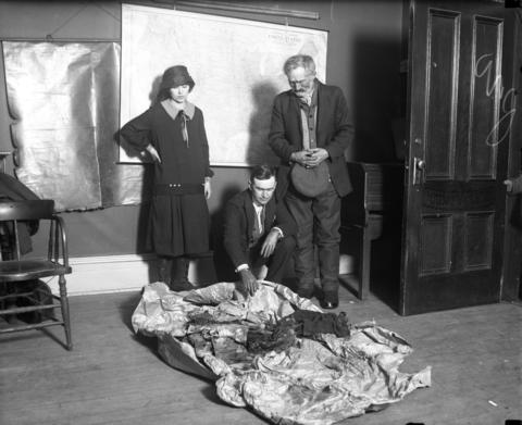 """Christ Olson, right, views his daughter Clara's clothes Dec. 6, 1926, at an inquest into her slaying in Prairie du Chien. With Olson is daughter Alice, 19. According to the Tribune, """"The body was clad in a tan coat, a red sweater, a greenish black silk dress, new shoes and stockings, and undergarments. A string of pearls around the neck had been broken."""""""
