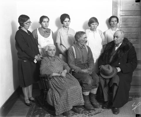 The family of Clara Olson: sisters Emma, 28, from left, Inga, 13, Alice, 19, Cornelia, 16, and Minnie, 34. Clara's parents, Dina Olson and Christ Olson, sit with District Attorney J.S. Earl in December 1926.