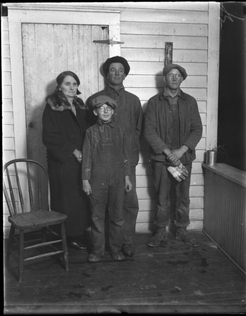 """Erdman Olson's mother, Mrs. Albert Olson, left, his younger brother Arvid Olson, front, and his father, Albert Olson, in 1926. Edwin Knutson, right, worked on the farm. Erdman was suspected of killing his lover, Clara Olson, because she was pregnant and wanted Erdman to marry her. Albert Olson told the Tribune, """"This whole thing grows out of an effort to make my boy marry that girl. I don't care how it turns out, they'll find out my boy didn't commit any crime. I have witnesses who saw him at a dance the night that girl went away."""""""