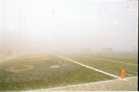 "Fog shrouds the Chicago Bears and Philadelphia Eagles as they huddle at Soldier Field on December 31, 1988, during the game that became known as ""Fog Bowl."""