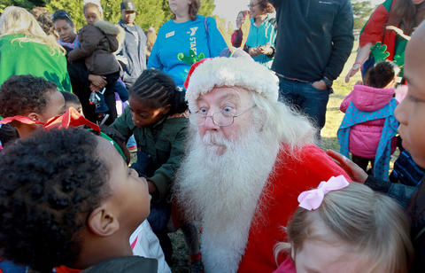 Staff Photo Of The Week: Dec 13-Dec 19, 2014      Santa Clause is swarmed by children at the Newport News YMCA after arriving by helicopter Wednesday. St. Nick was played by John Howard of Newport News.
