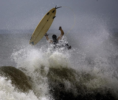A surfer kicks out of a wave at Buckroe Beach Friday. Waves created by Hurricane Earl had drawn numerous surfers the the beach by midday.
