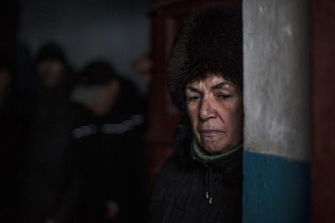 A Ukrainian woman waits inside a building for shelling to stop in the Kievsky district in Donetsk, Ukraine, on Tuesday, Jan. 20, 2015.
